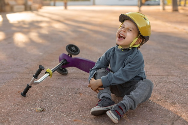 Little boy outdoors hurt from the feel of scooter