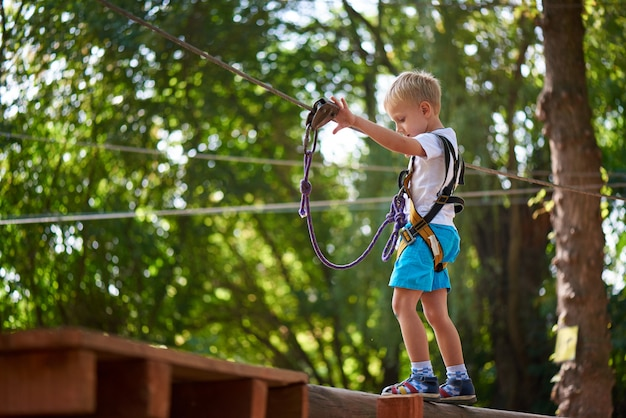 Little boy overcomes the obstacle in the rope park.