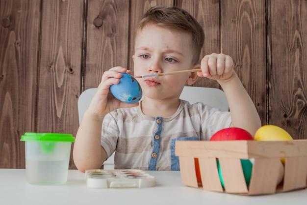 Маленький мальчик красит красочные пасхальные яйца на деревянной стене