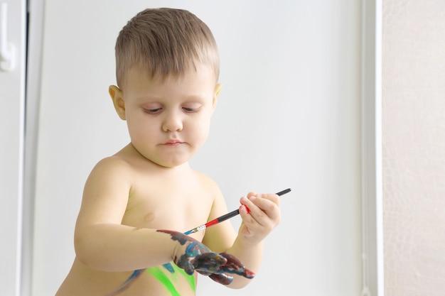 어린 소년 페인트는 당신의 손을 페인트합니다. 어린이 발달의 예술적 창의성