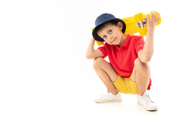 A little boy in panama, yellow jersey, red shorts and white sneakers sits and holds a yellow penny in his hands