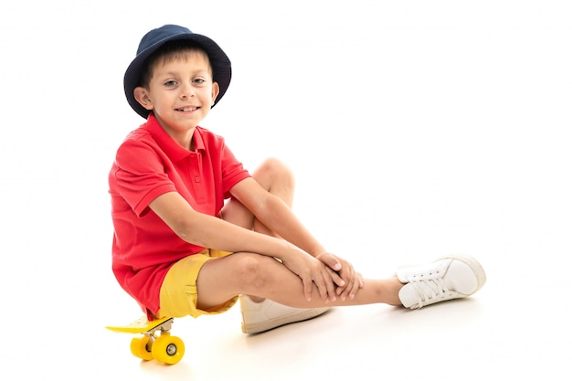 A little boy in panama, yellow jersey, red shorts and white sneakers sits on a yellow penny and smiles