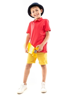 A little boy in panama, yellow jersey, red shorts and white sneakers stands and holds a yellow penny in his hands