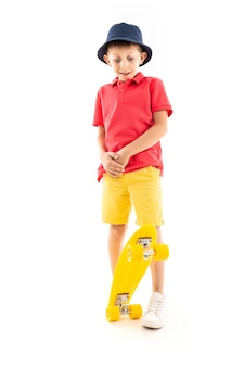 A little boy in panama, yellow jersey, red shorts and white sneakers stands and holds a yellow penny