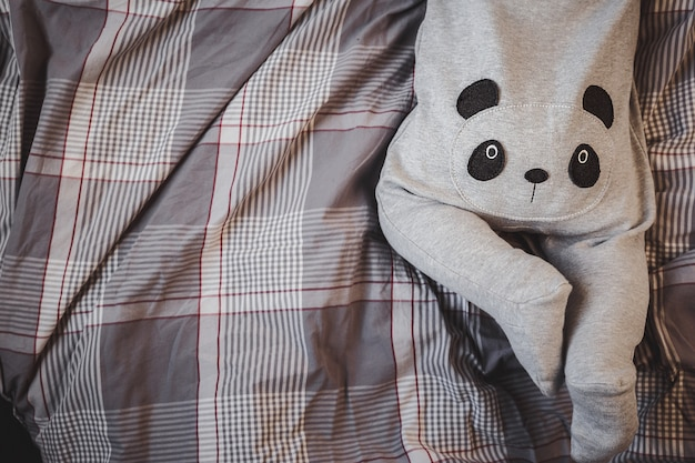 Little boy in a panda costume lies on the bed. ass baby