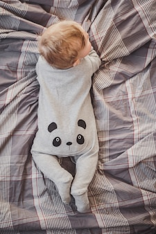 Little boy in a panda costume lies on the bed.
