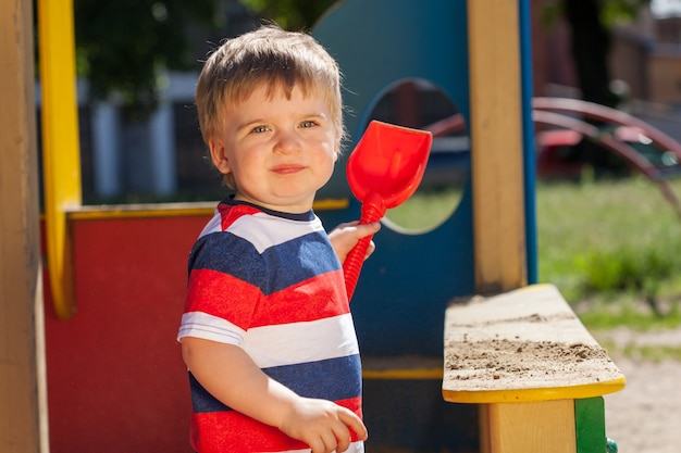 Little boy in the park on the playground. in a colored striped t-shirt with a red shovel. high quality photo