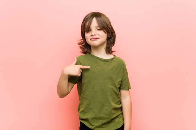 Little boy person pointing by hand to a shirt copy space, proud and confident