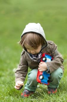 Little boy picking up a small flower