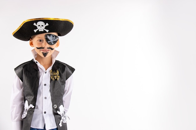 A little boy in a pirate costume and a makeup on his face is having a good time at the halloween party.