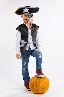 Little boy in a pirate costume and with a huge pumpkin in full growth, looking at the camera on a white wall.