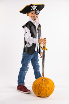 Little boy in a pirate costume and with a huge pumpkin looking at the camera on a white wall .