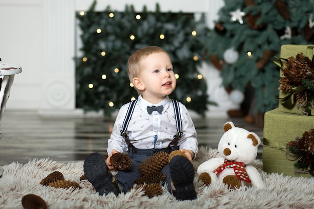 Little boy play with pine cones  near a christmas tree.