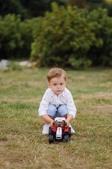 小さな男の子は芝生の上のおもちゃの車で遊ぶ