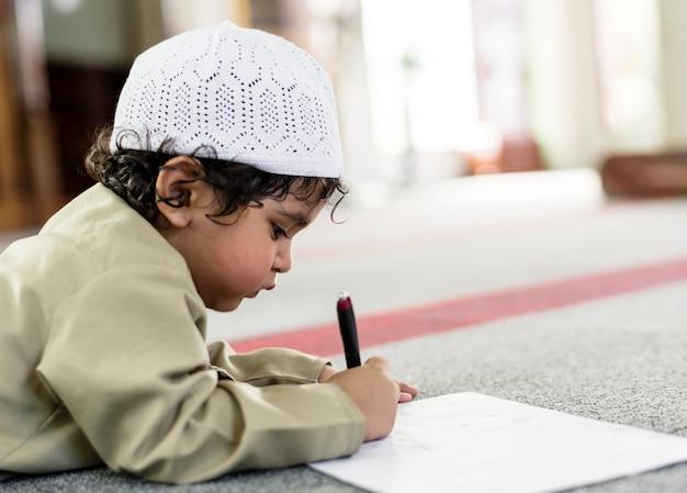 ラマダンの間にモスクのいたずらに描く小さな男の子