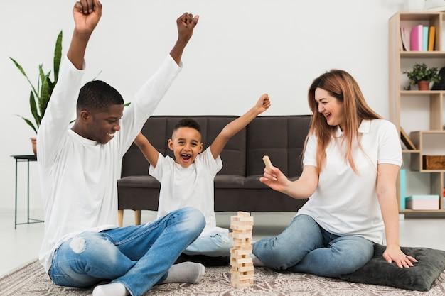 屋内で両親とゲームをする少年