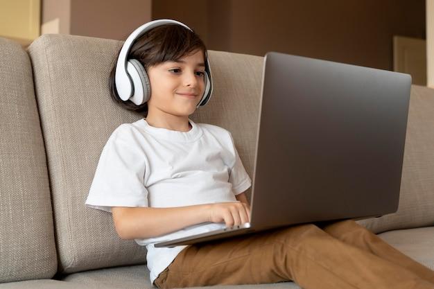 彼のラップトップでビデオゲームをしている小さな男の子