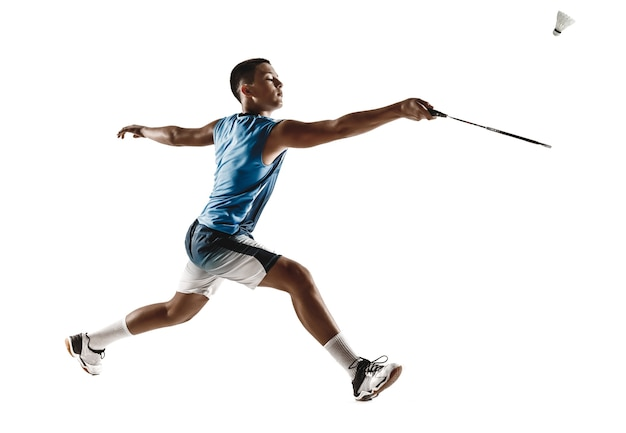 어린 소년 흰색 스튜디오 배경에 고립 배드민턴. 스포츠웨어와 운동화의 젊은 남성 모델, 행동 라켓, 게임에서의 움직임. 스포츠, 운동, 건강한 라이프 스타일의 개념.