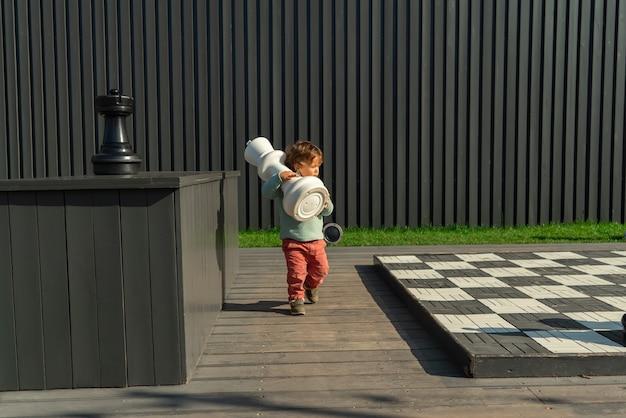 Маленький мальчик играет в большие шахматы на детской площадке на открытом воздухе на фоне черной стены.