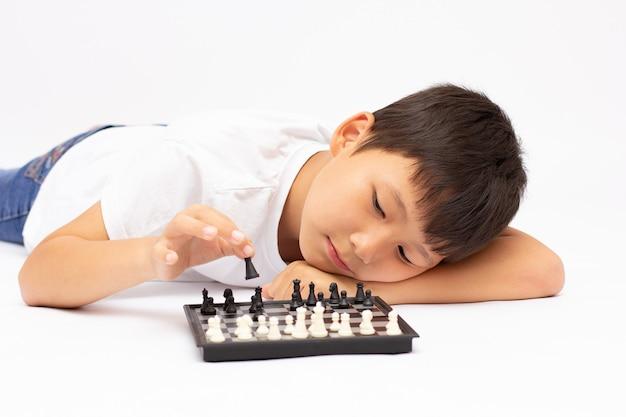 地面でチェスをしている小さな男の子
