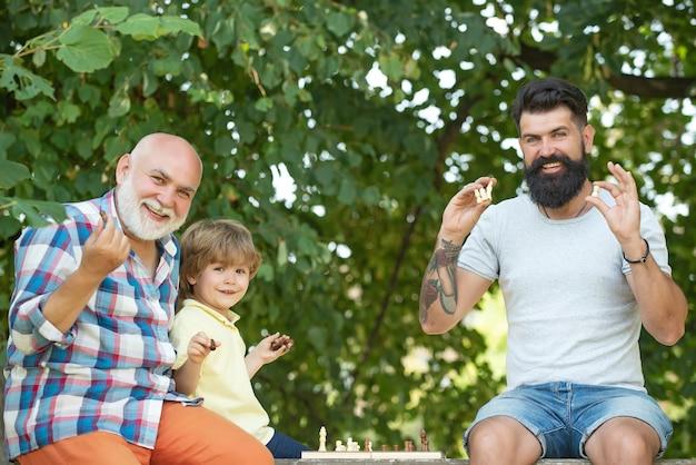 彼の祖父と父とチェスをしている小さな男の子