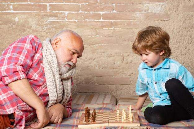 祖父とチェスをしている少年。チェスの駒。彼の次の動きについて考えている年配の男性