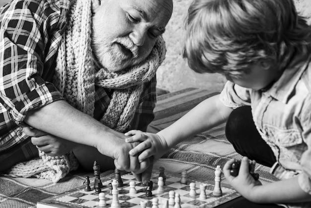 祖父とチェスをしている少年