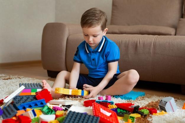 Маленький мальчик играет в конструктор на полу