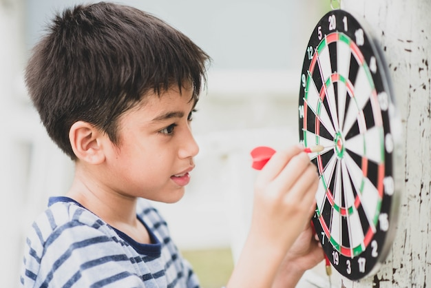 Little boy playing darts board family outdoor activity
