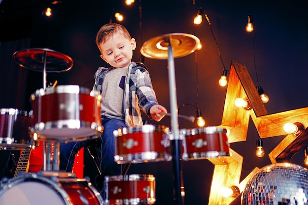 Little boy playing the drums on the stage