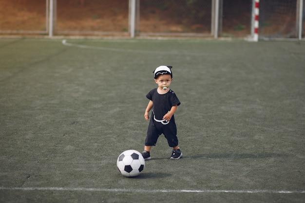 Маленький мальчик играет в футбол на спортивной площадке