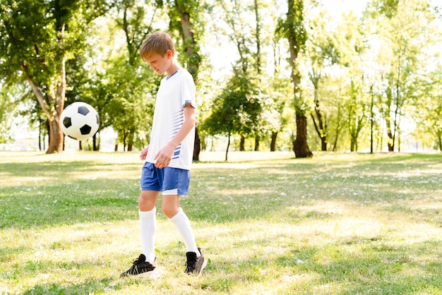 Little boy playing football with copy space