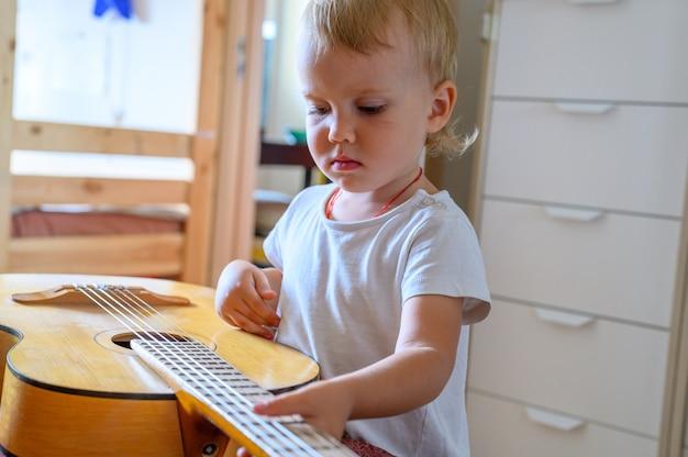 自宅でギターを弾く少年