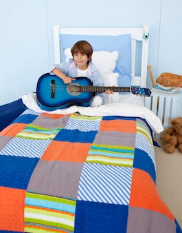 Little boy playing guitar in bedroom