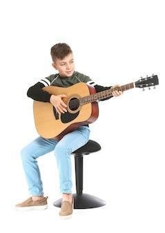 Маленький мальчик играет на гитаре на белой поверхности