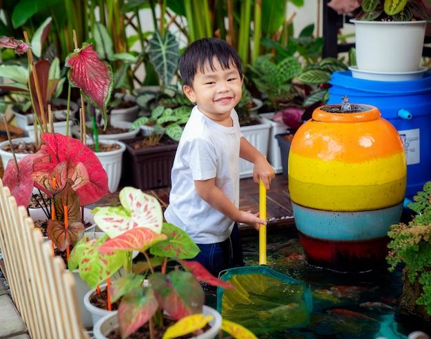 Маленький мальчик играет в пруду с карпами кои