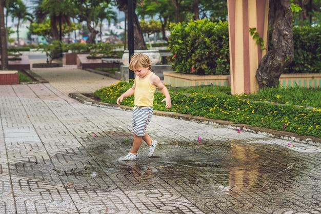 Маленький мальчик играет в луже