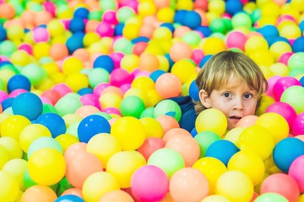 Маленький мальчик играет в бассейне с красочными пластиковыми шарами