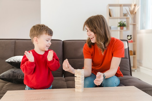 Little boy playing janga with his mom