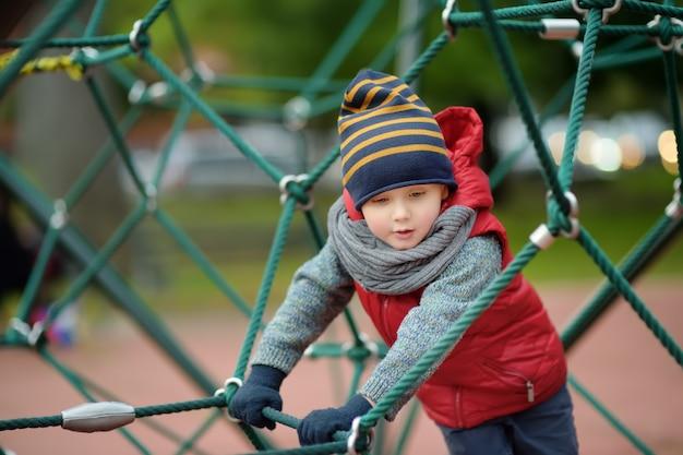Little boy playing on modern kids play ground.