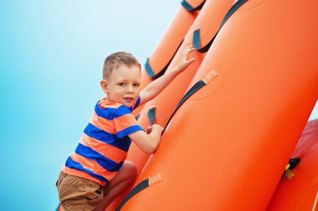 Маленький мальчик играет на надувной детской площадке на пляже в летний день.