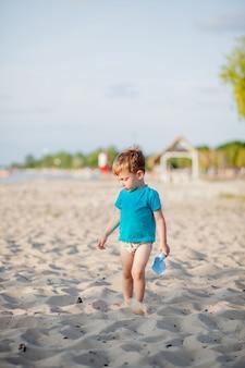 Маленький мальчик играет на пляже с пластиковой лопатой