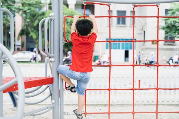 遊び場のジャングルジムで遊ぶ少年