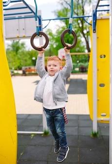 遊び場で遊んでいる小さな男の子。
