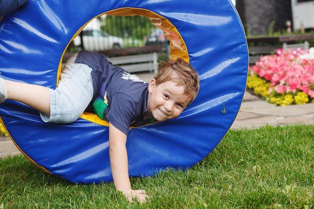 Маленький мальчик играет на детской площадке.