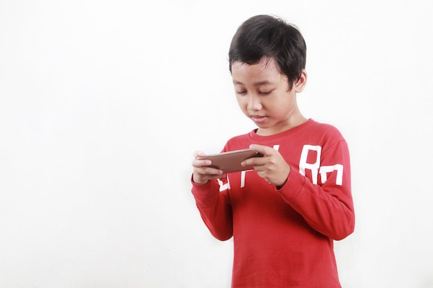 Little boy playing online games on a smartphone application
