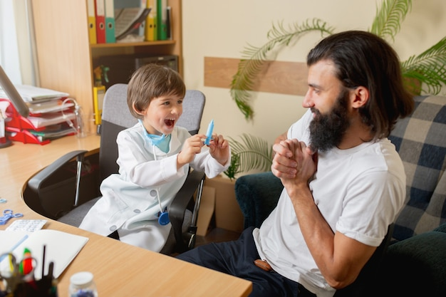 Little boy playing pretends like doctor examining a man in comfortabe medical office. healthcare, childhood, medicine, protection and happiness concept. having fun, laughting while giving pills