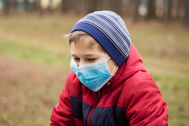 Little boy playing on public playground in medical mask to protect himself from covid-19