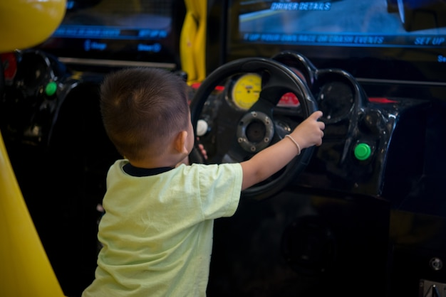 Little boy playing in the race behind the wheel of a game console