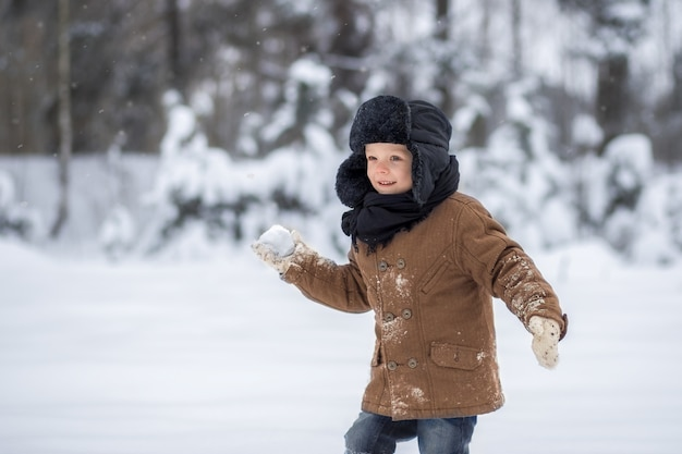 Little boy playing snowballs in winter